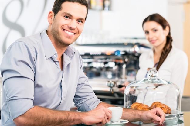 Portret van de knappe jonge man tijdens het ontbijt binnenshuis op een gezellige locatie