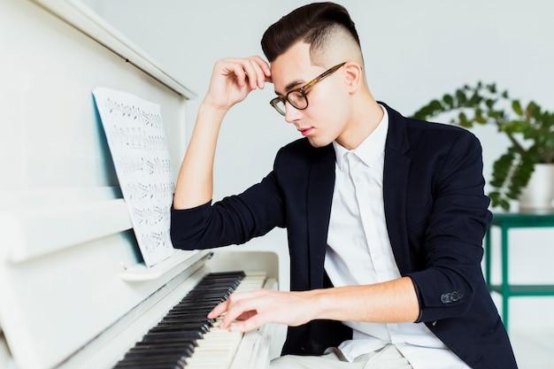 Portret van de knappe jonge mens die de piano speelt
