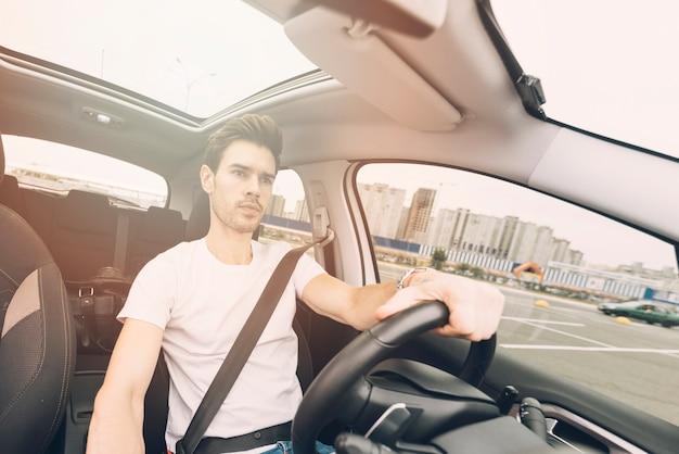 Portret van de knappe jonge mens die een auto drijft