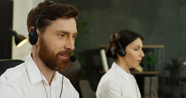 Portret van de knappe jonge mens in hoofdtelefoon die bij computer in call centre werkt.