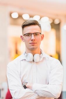 Portret van de knappe jonge mens met gekruiste wapens die witte hoofdtelefoon houden rond zijn hals