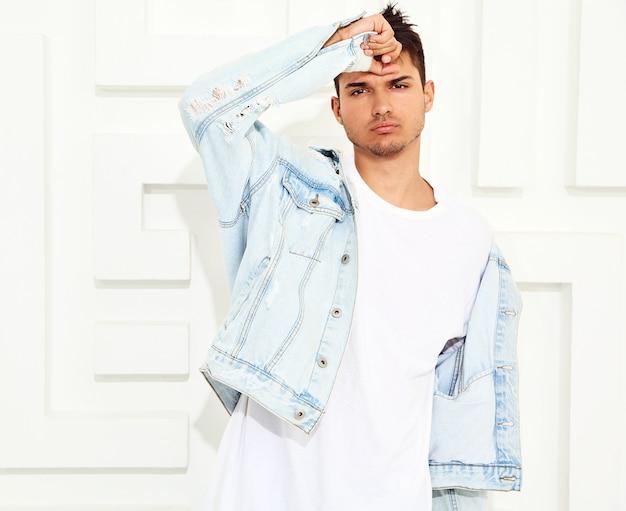 Portret van de knappe jonge modelmens gekleed in jeanskleren die dichtbij witte geweven muur stellen