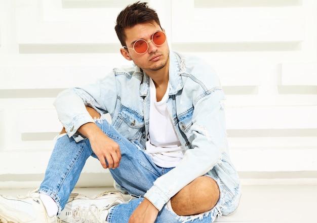 Portret van de knappe jonge modelmens gekleed in jeanskleren die dichtbij witte geweven muur zitten