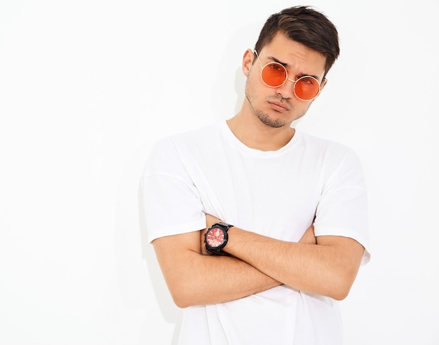 Portret van de knappe jonge modelmens gekleed in jeanskleren en t-shirt in zonnebril het stellen. gekruiste armen