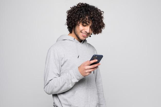 Portret van de knappe krullende telefoon van de mensenholding die op witte muur wordt geïsoleerd
