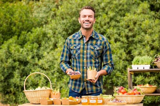 Portret van de knappe man die biologische groenten verkoopt