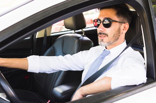 Portret van de knappe mens die de auto drijft