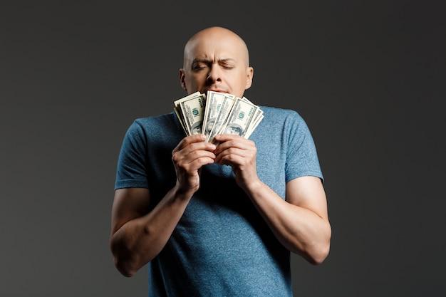 Portret van de knappe mens in het grijze geld van de overhemdsholding over donkere muur
