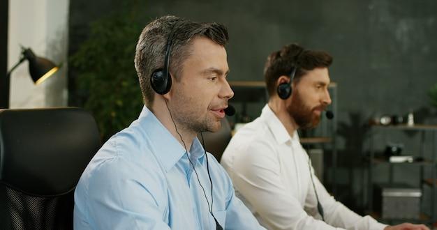 Portret van de knappe mens in hoofdtelefoon die bij computer in call centre werken