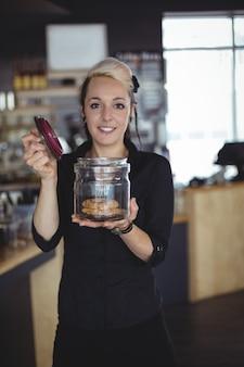 Portret van de kruik van de serveersterholding koekjes bij teller