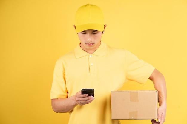 Portret van de ladingsdoos van de leverings mannelijke holding en het gebruiken van telefoon op gele muur