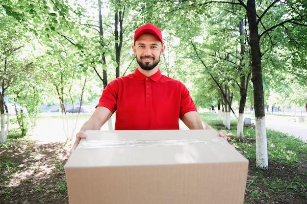 Portret van de leveringsmens die pakket uitdeelt