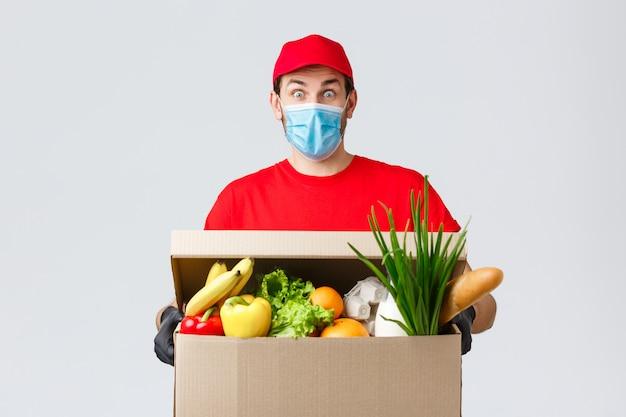 Portret van de leveringsmens met gezichtsmasker en kruidenierswinkeldoos