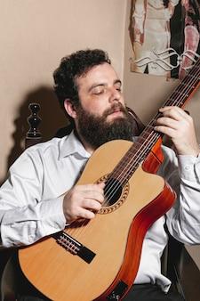 Portret van de mens die akoestische gitaar speelt