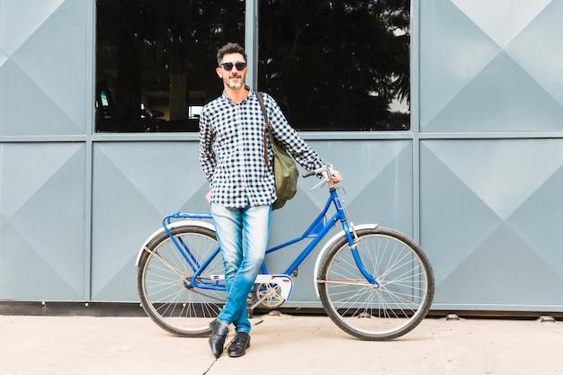 Portret van de mens die dichtbij zijn blauwe fiets met zijn rugzak leunt