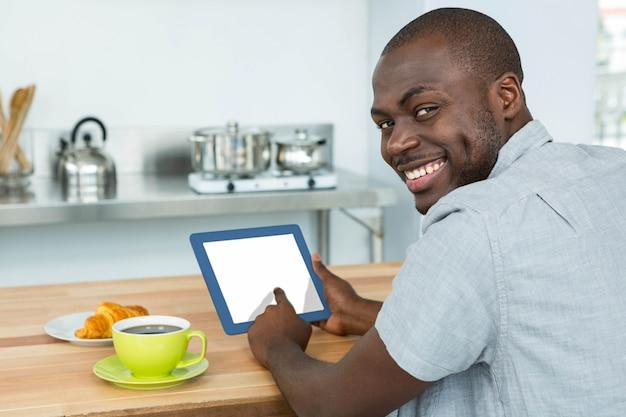 Portret van de mens die digitale tablet gebruiken terwijl het hebben van ontbijt in keuken