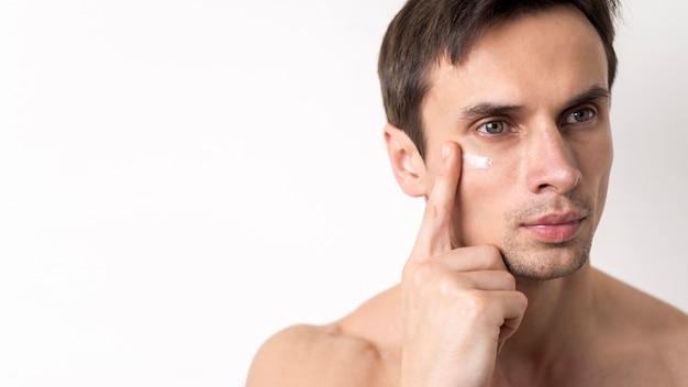 Portret van de mens die gezichtsroom toepast