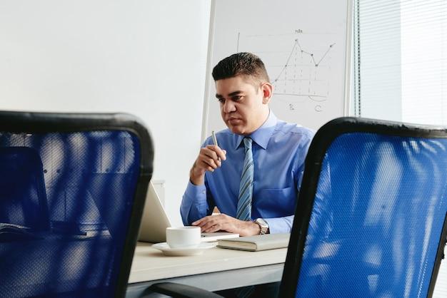 Portret van de mens die in het bureau bij laptop werkt