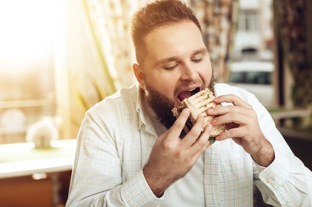 Portret van de mens die in koffie eet en van voedsel geniet