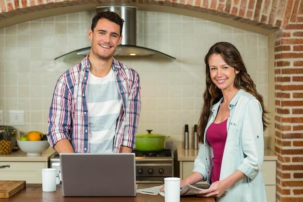 Portret van de mens die laptop en vrouwenlezingskrant op keuken met behulp van worktop