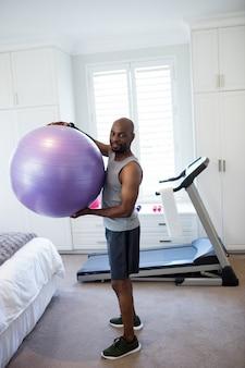 Portret van de mens die met geschiktheidsbal uitoefenen in slaapkamer