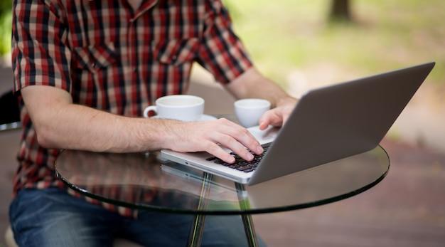 Portret van de mens die met laptop werkt