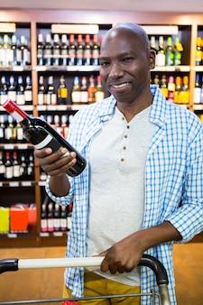 Portret van de mens die wijnfles bekijken in kruidenierswinkelsectie