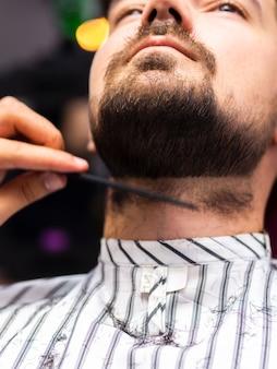Portret van de mens die zijn baardbesnoeiing krijgt