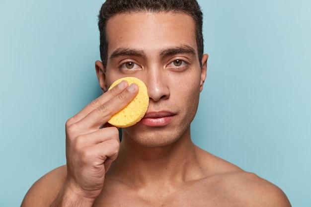 Portret van de mens die zijn gezicht met spons schoonmaakt
