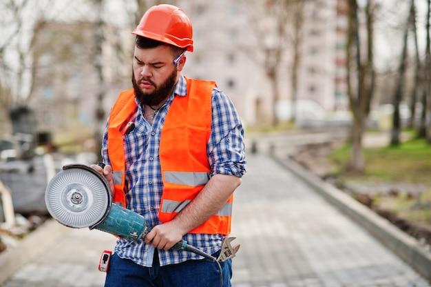 Portret van de mens het kostuumbouwvakker van de baardarbeider in veiligheids oranje helm tegen bestrating met in hand hoekige malende machine.