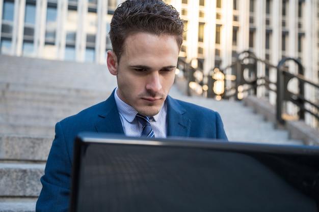 Portret van de mens in elegant kostuum die aan treden met laptop op knieën werken.
