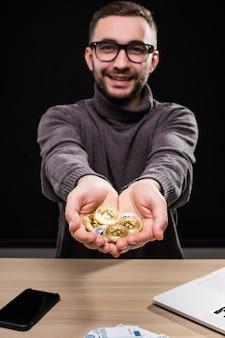 Portret van de mens in glazen die gouden bitcoins in zijn handen tonen bij bureau dat over zwart wordt geïsoleerd