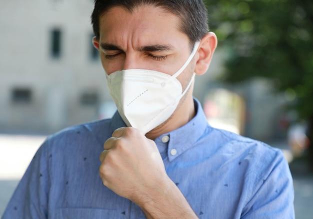 Portret van de mens met gezichtsmasker tegen sars-cov-2 openlucht hoesten.