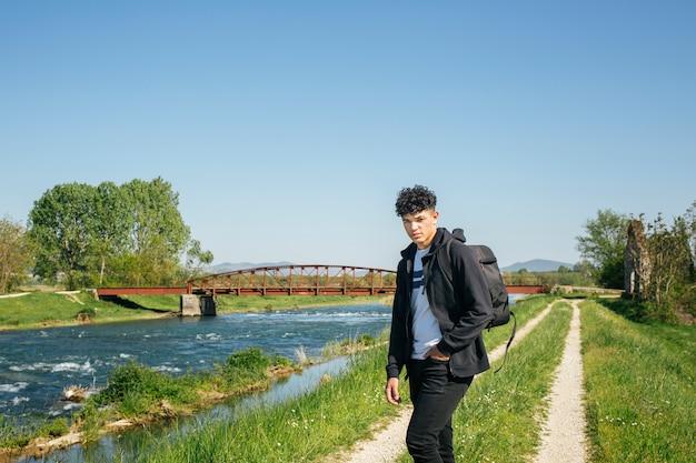 Portret van de mens met rugzak die zich dichtbij rivier bevindt