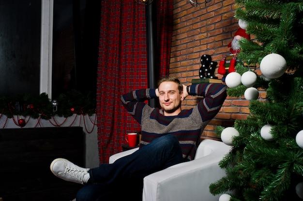 Portret van de mens tegen kerstboom met decoraties.