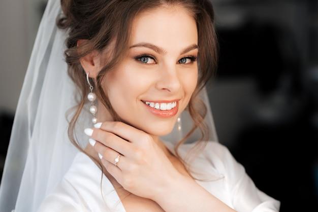 Portret van de mooie bruid wat betreft haar oorringen en het glimlachen
