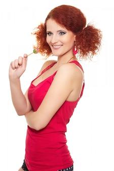 Portret van de mooie glimlachende vrouw van de roodharigegember in rode die doek met snoepje op wit wordt geïsoleerd