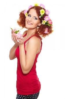 Portret van de mooie glimlachende vrouw van de roodharigegember in rode doek met gele roze kleurrijke bloemen in haar dat op witte holdingsbloemen wordt geïsoleerd