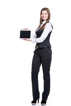 Portret van de mooie jonge gelukkige tablet van de bedrijfsvrouwenholding met het lege scherm in volle lengte - dat op wit wordt geïsoleerd.