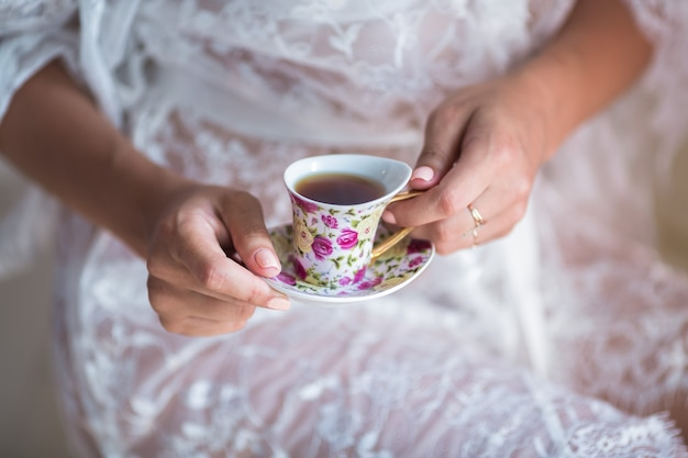 Portret van de mooie jonge vrouw die 's ochtends thee drinkt close-up. vrouwenhanden met een kopje thee