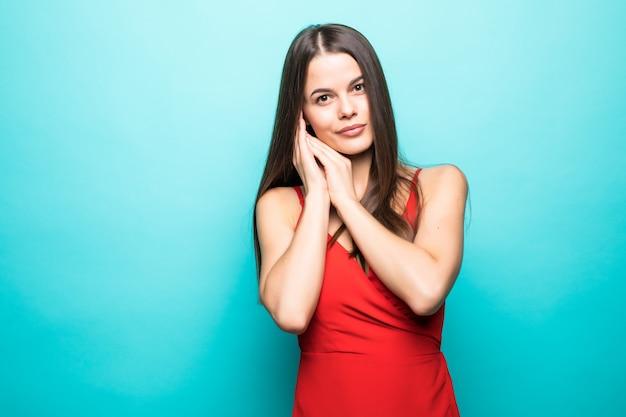 Portret van de mooie jonge vrouw in rode jurk op de blauwe muur