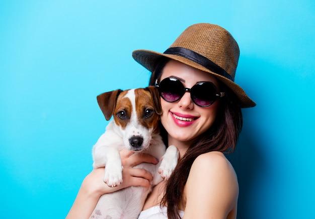 Portret van de mooie jonge vrouw met hond op de blauwe achtergrond