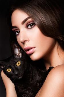 Portret van de mooie jonge vrouw met kat