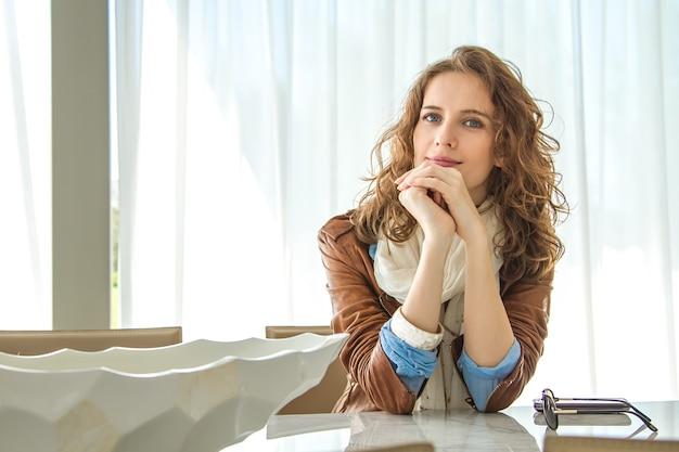 Portret van de mooie langharige vrouw zittend aan een tafel in een modern interieur binnenshuis.