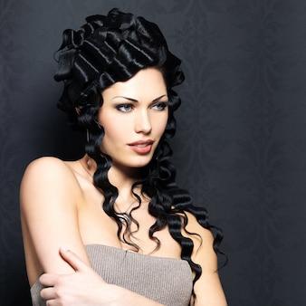 Portret van de mooie mode sexy vrouw met lang krullend kapsel vormt binnen