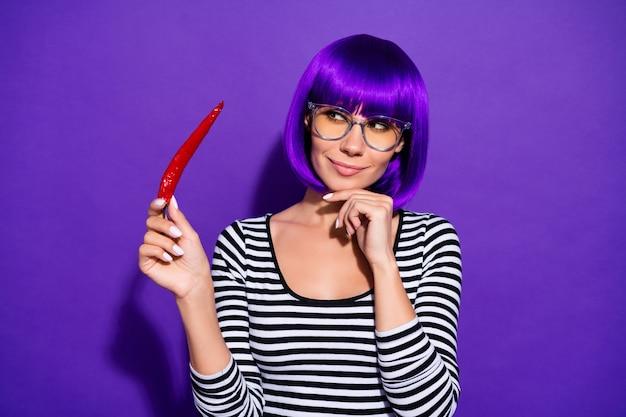 Portret van de mooie peper die van de persoonsholding met gedachten kijkt gekleed gestreept overhemd dat over purpere violette achtergrond wordt geïsoleerd