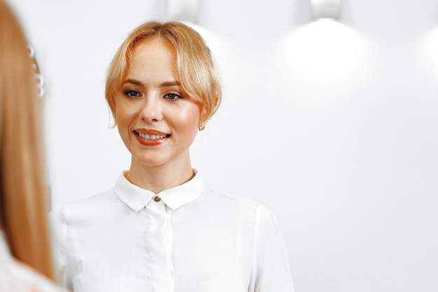 Portret van de mooie receptioniste van het blonde vrouwenhotel