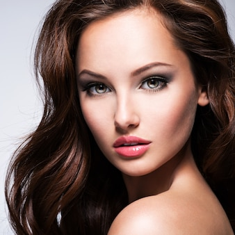 Portret van de mooie vrouw met bruin krullend haar die zich voordeed op donkere achtergrond