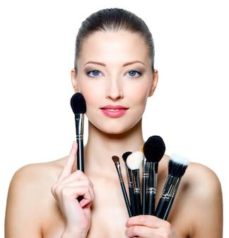 Portret van de mooie vrouw met make-upborstels dichtbij aantrekkelijk gezicht. volwassen girll poseren over witte ruimte