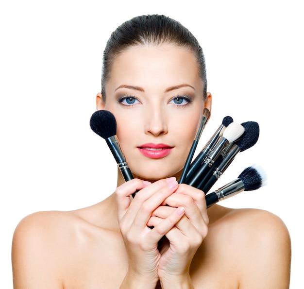 Portret van de mooie vrouw met make-upborstels dichtbij aantrekkelijk gezicht.